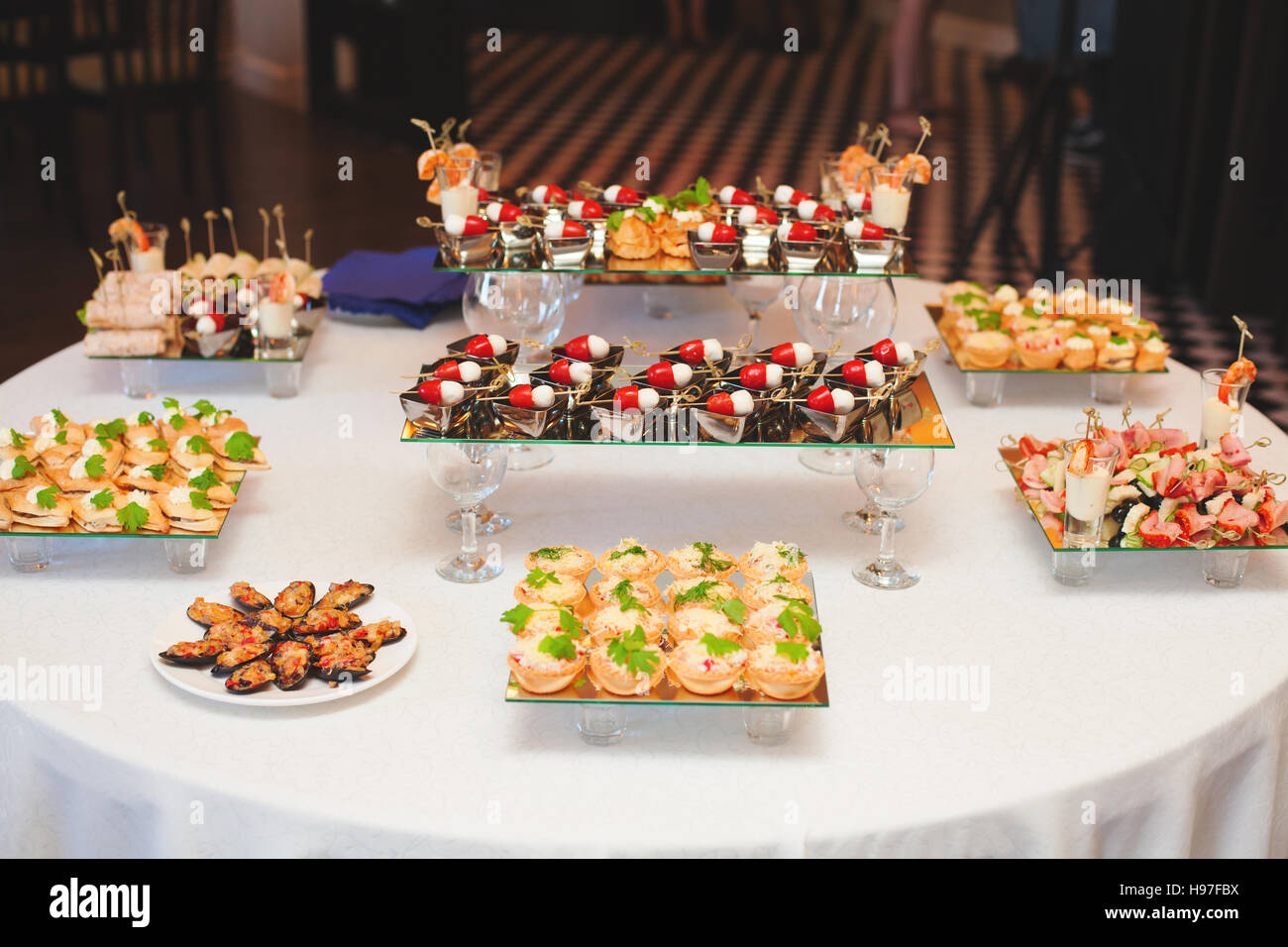 Table with assortment of canapes snacks. Banquet service. - Stock Image