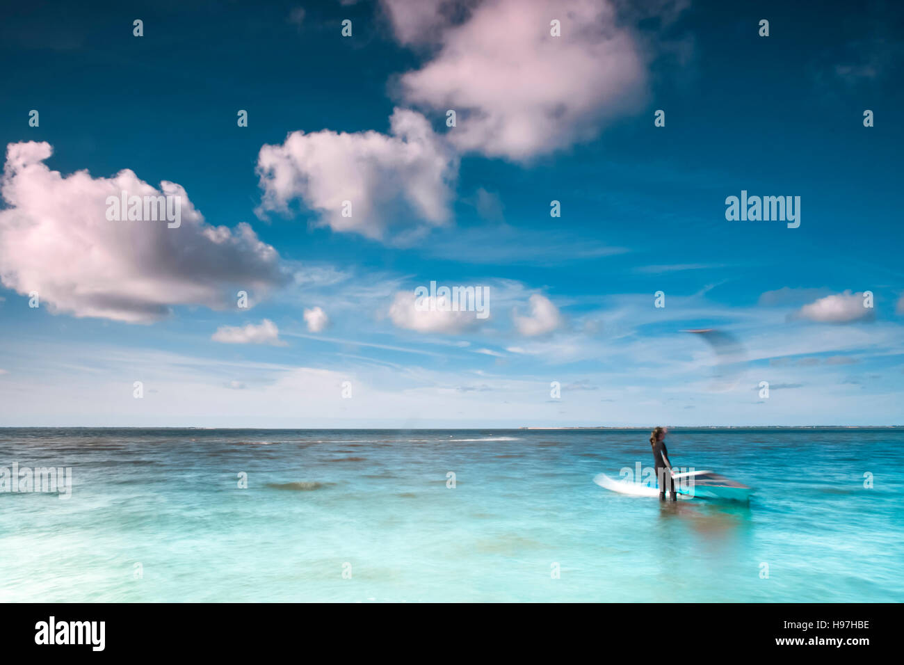 Wind surfer on his board on a calm ocean at the North Sea on a sunny blue sky day with clouds in a marine or nautical - Stock Image