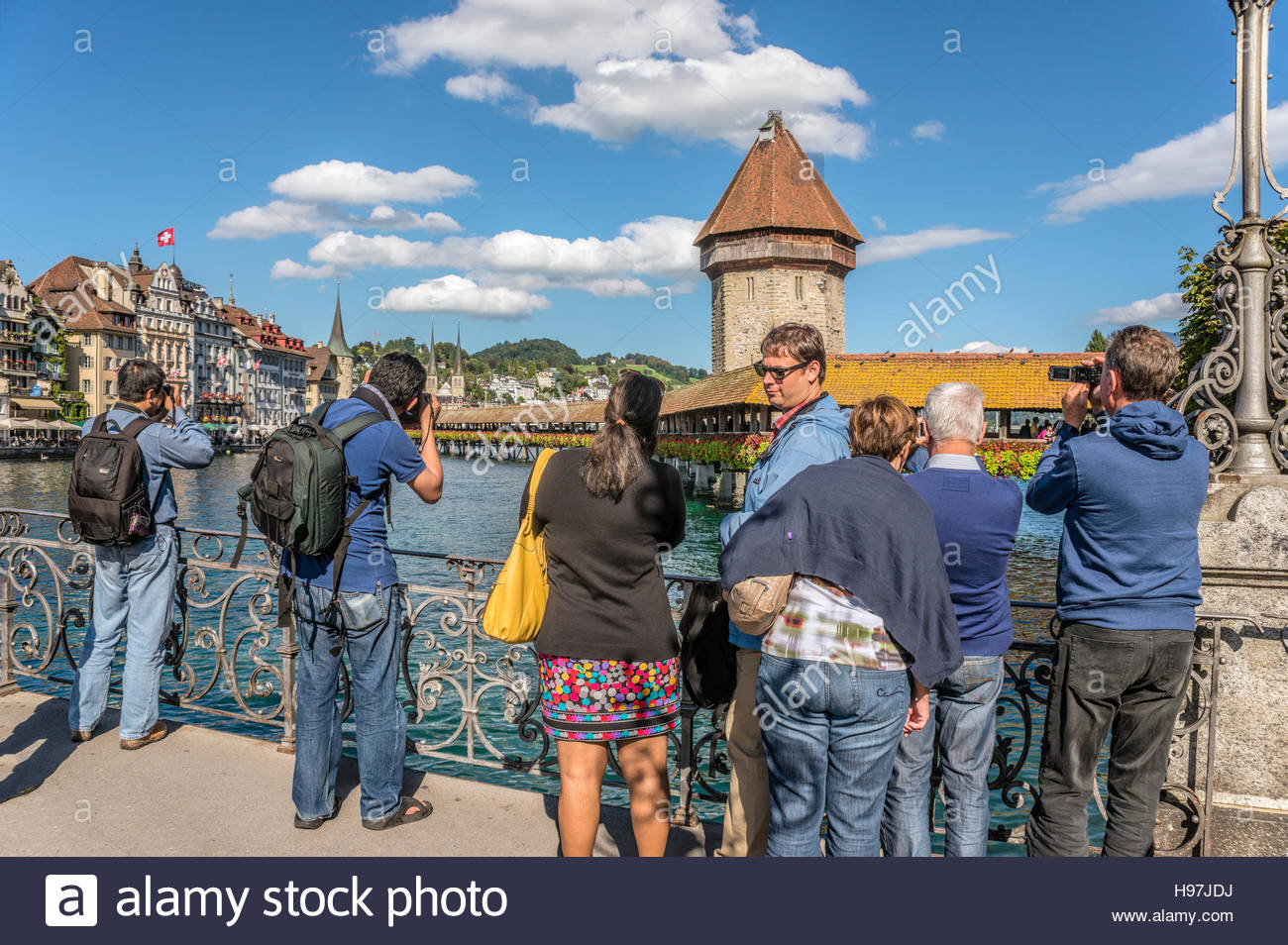 Group of Tourists taken pictures of the old town and Chapel Bridge, Lucerne, Switzerland. | Touristengruppe machen - Stock Image
