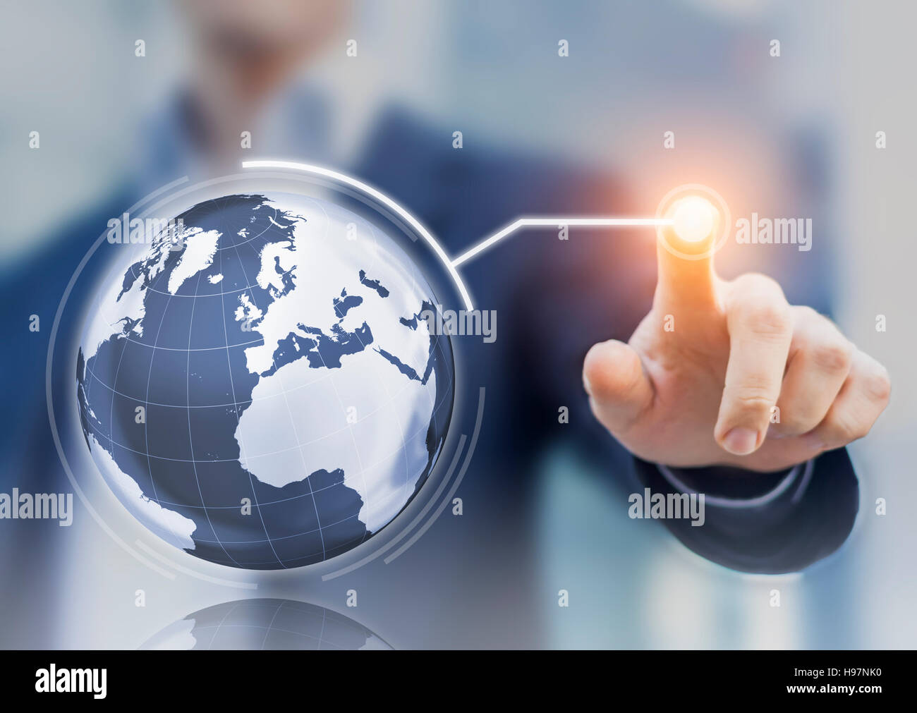Worldwide business concept with 3D globe interface and businessman touching a button, global economy - Stock Image