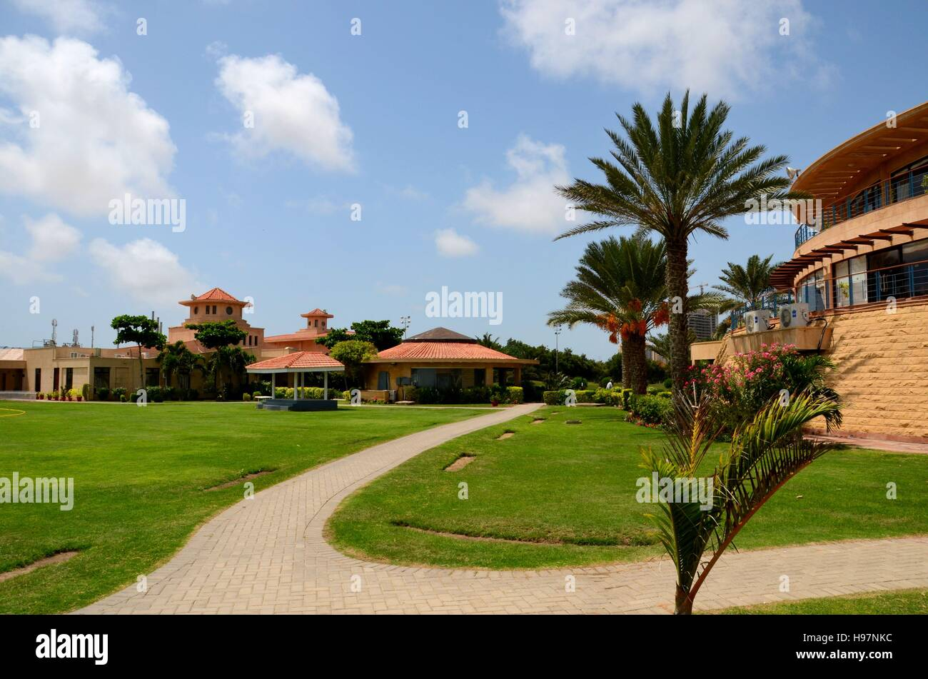 Clubhouse and gardens with pedestrian path at DHA Golf club
