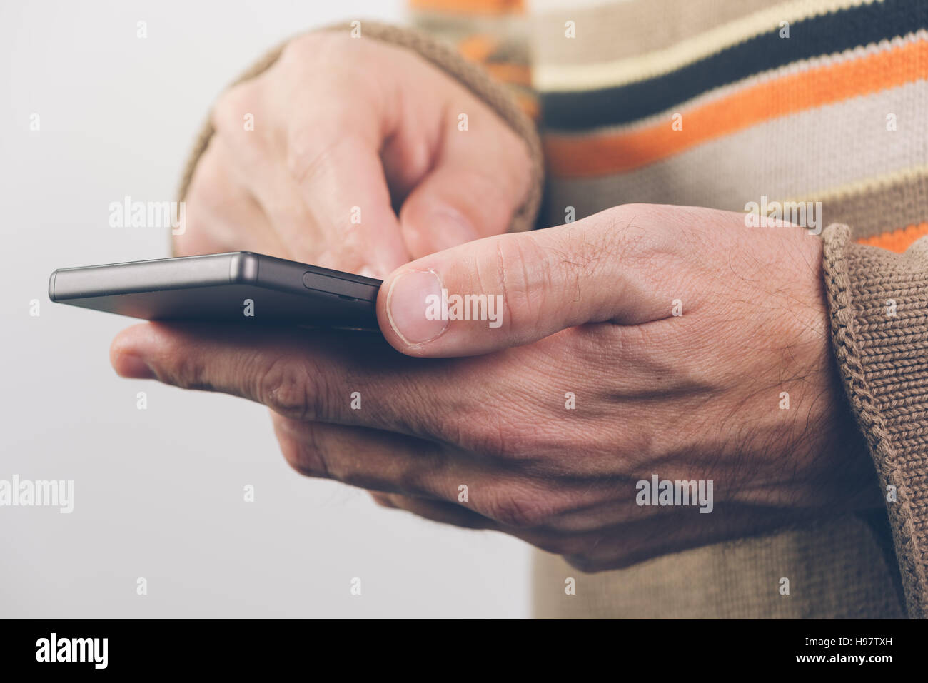 Using mobile phone for texting SMS message - Stock Image
