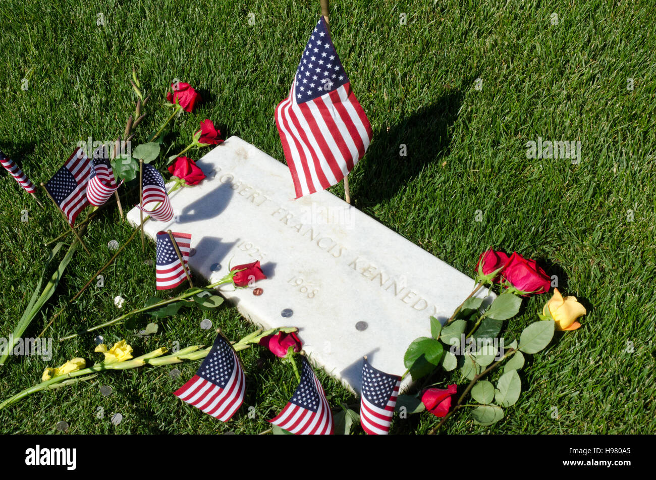 Grave of Robert F Kennedy - decorated with roses, flags, and coins - at Arlington National Cemetery near Washington, - Stock Image