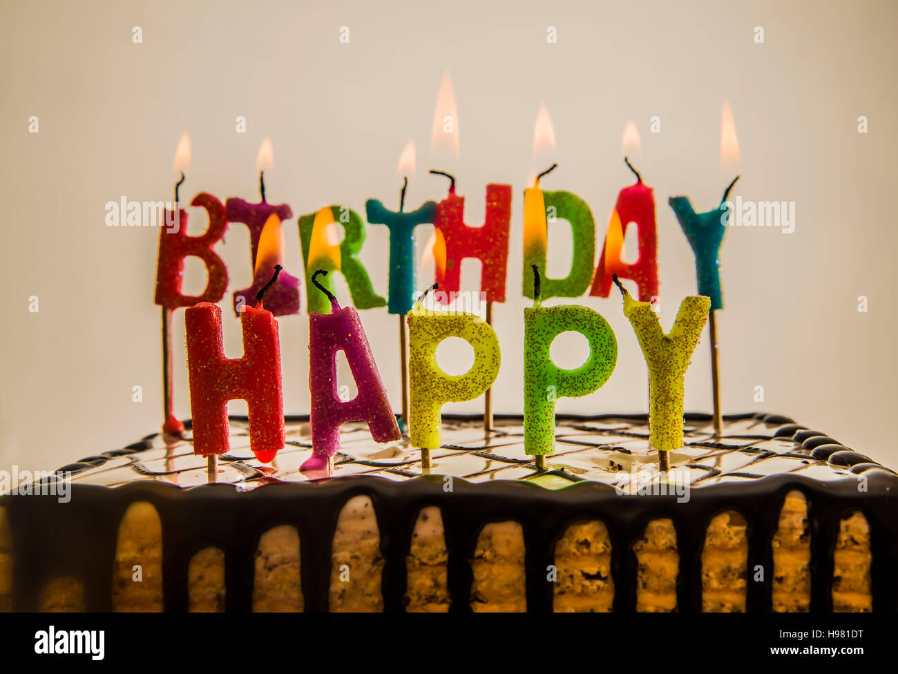 Happy Birthday Candles Burning On Chocolate Cake Isolated On White