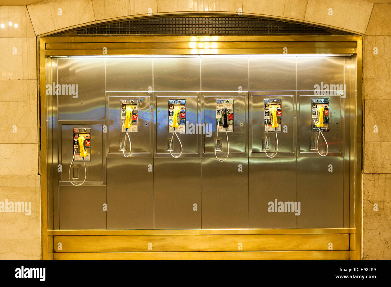 A wall installation of several traditional public pay phones in a row at Grand Central Station, New York City, NY, - Stock Image