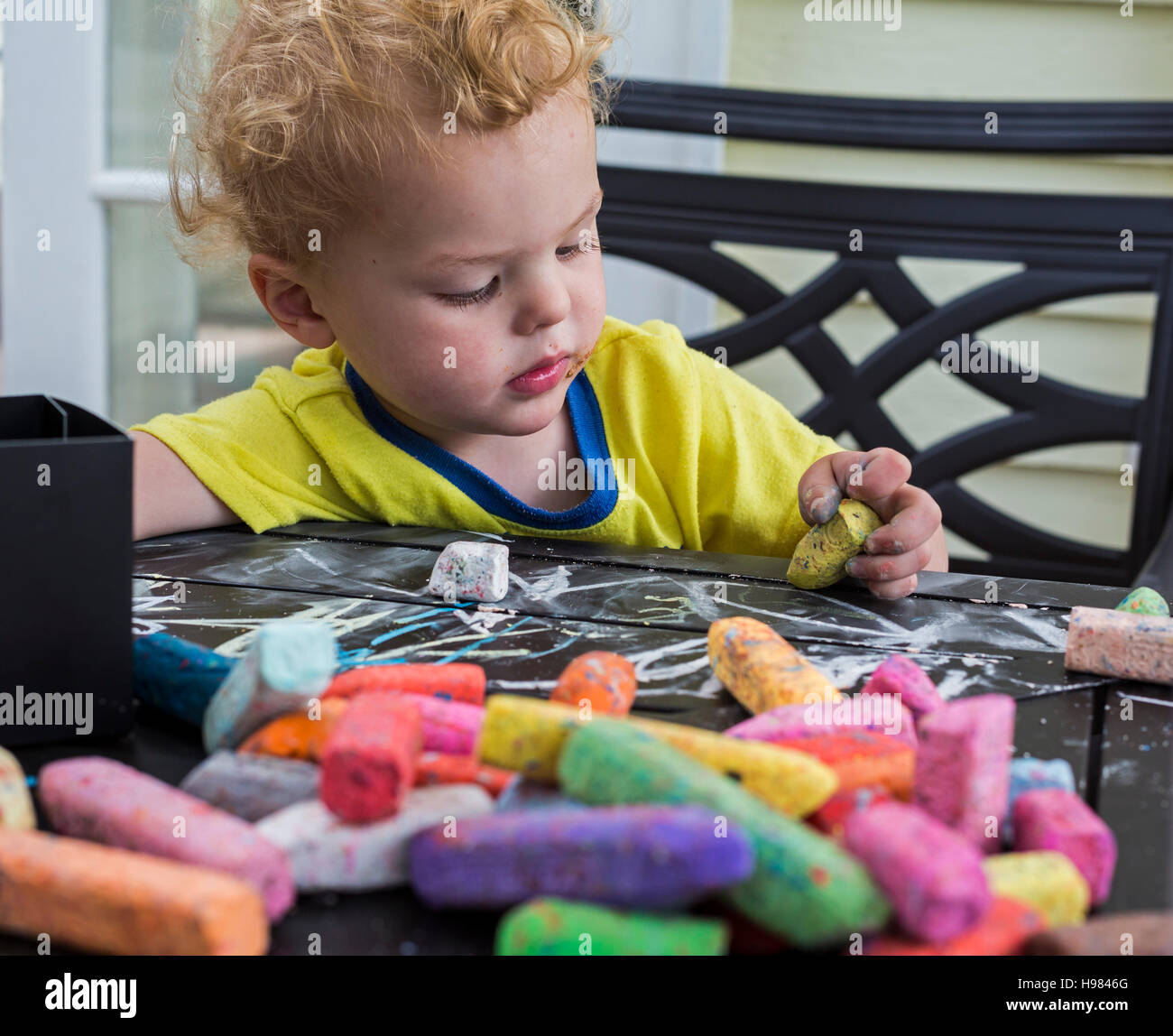 Denver, Colorado - Adam Hjermstad Jr., age 2, plays with chalk. - Stock Image