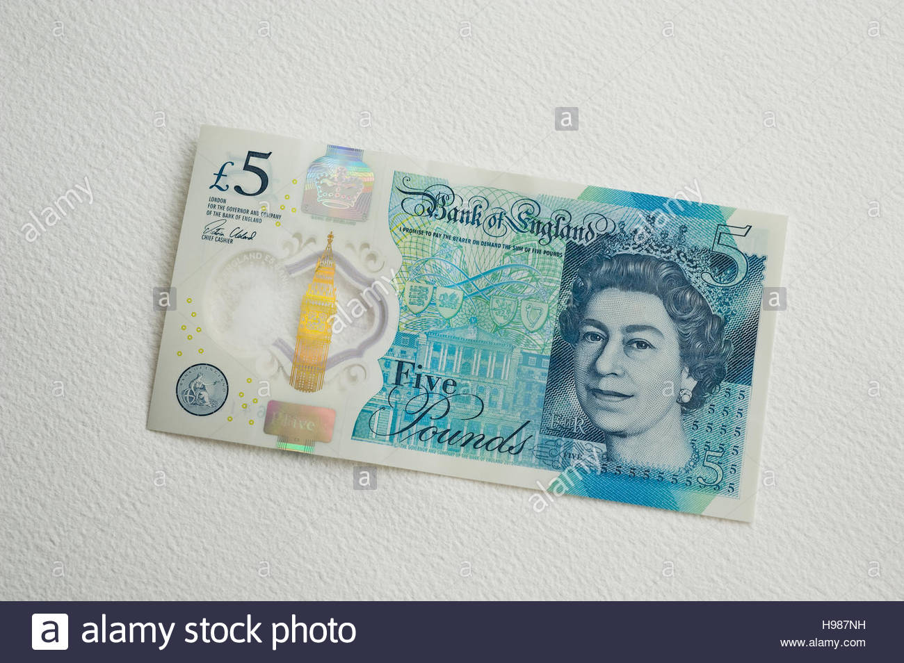 One new British sterling five pound notes with security features, see-through window and metallic image. - Stock Image