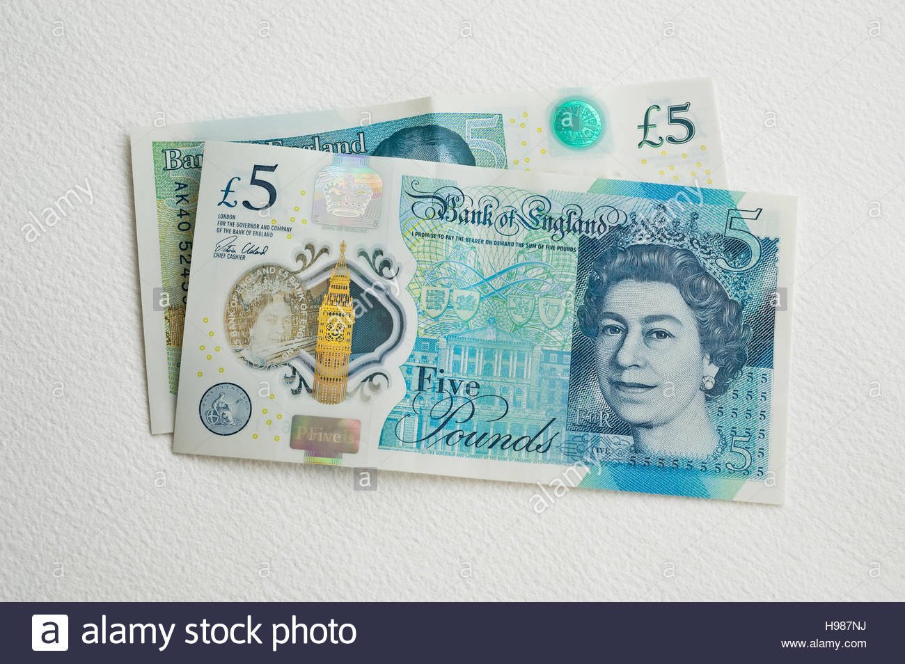 Two new British sterling five pound notes with security features, see-through window and metallic image. - Stock Image