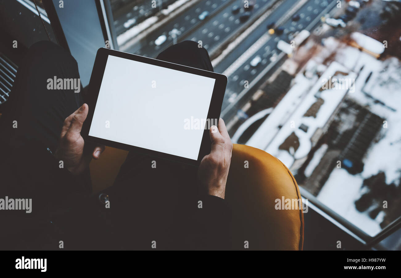 Close up view of mock up template of tablet pc in hands of man sitting near window of skyscraper, using digital Stock Photo
