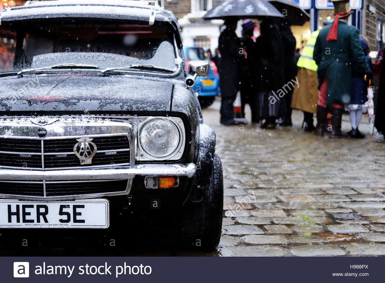 A black mini converted into a hearse, with an AA badge, at a steampunk festival. - Stock Image