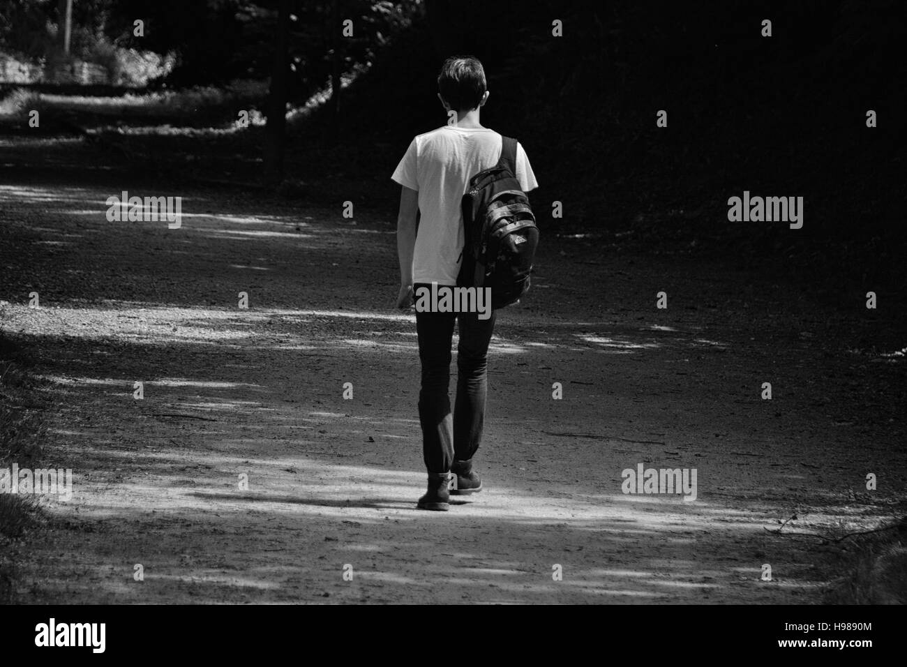 School boy walking a path with back pack in black and white - Stock Image