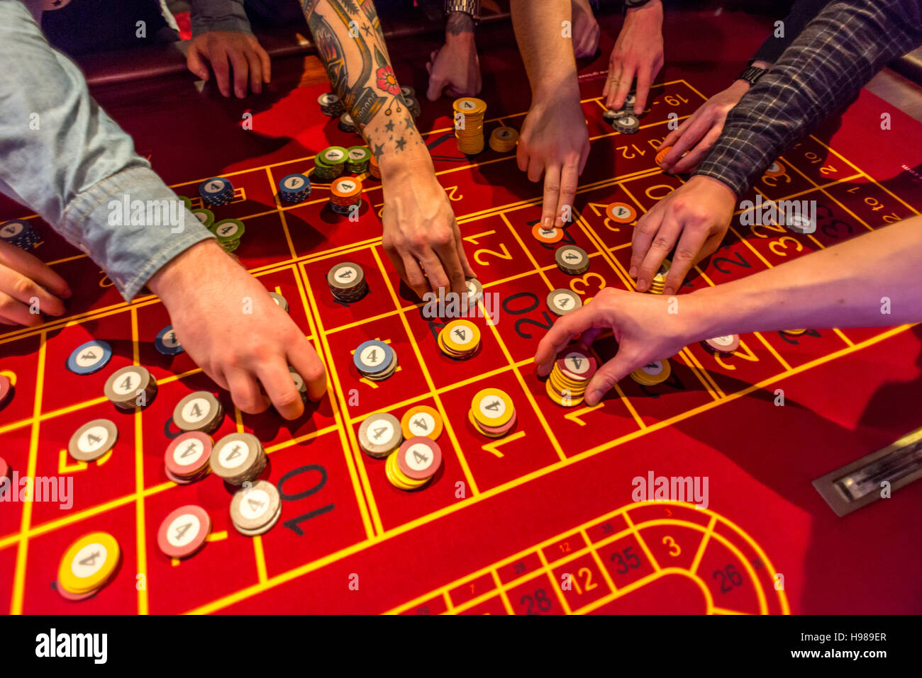 Young men on a night out gambling and playing roulette - Stock Image