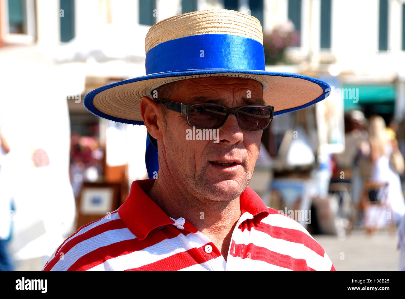 Gondolier with the typical headgear at Grand Canal of Venice in Italy. - Stock Image