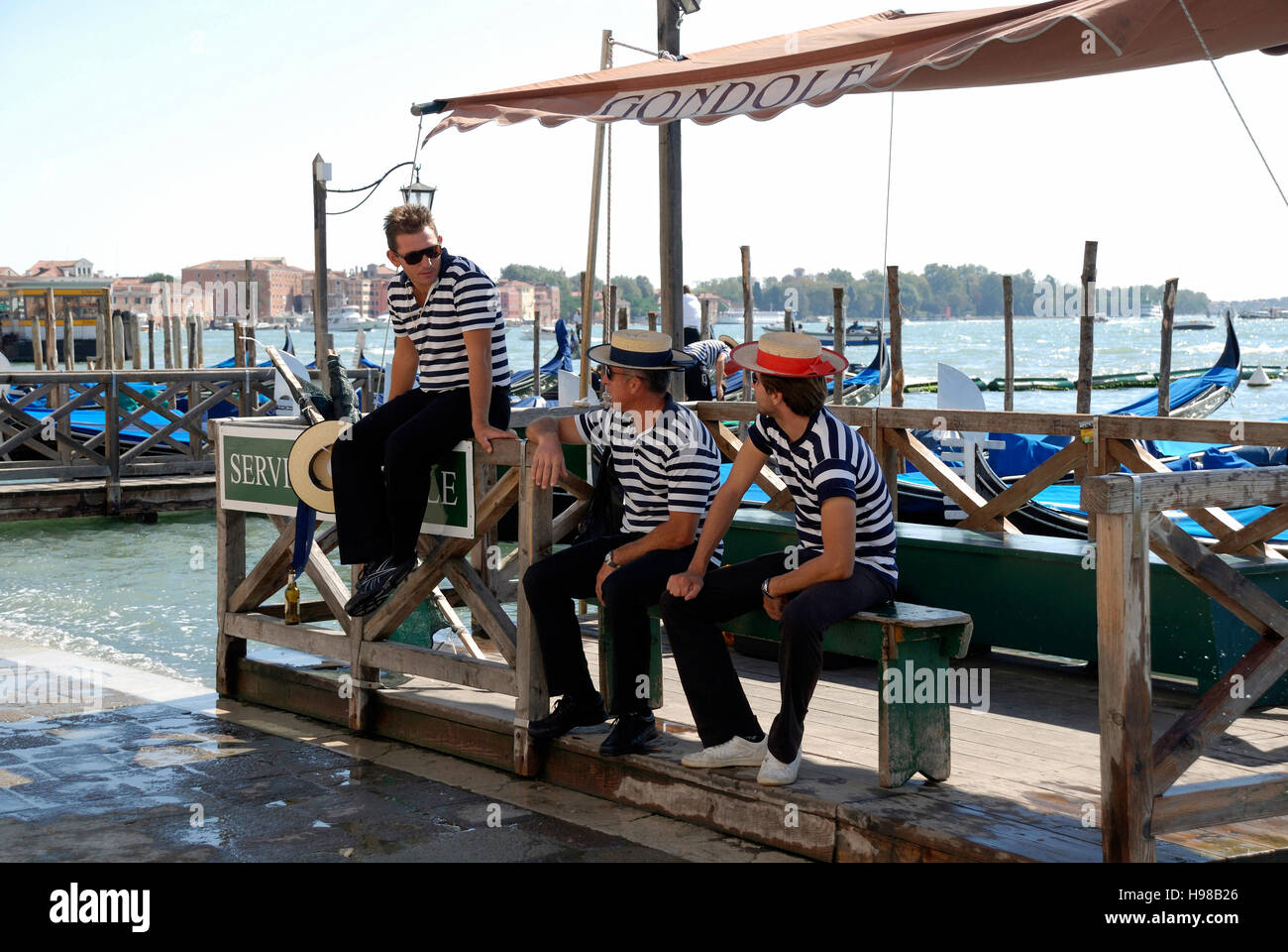 Gondoliers with the typical headgear on a Grand Canal of Venice in Italy. - Stock Image