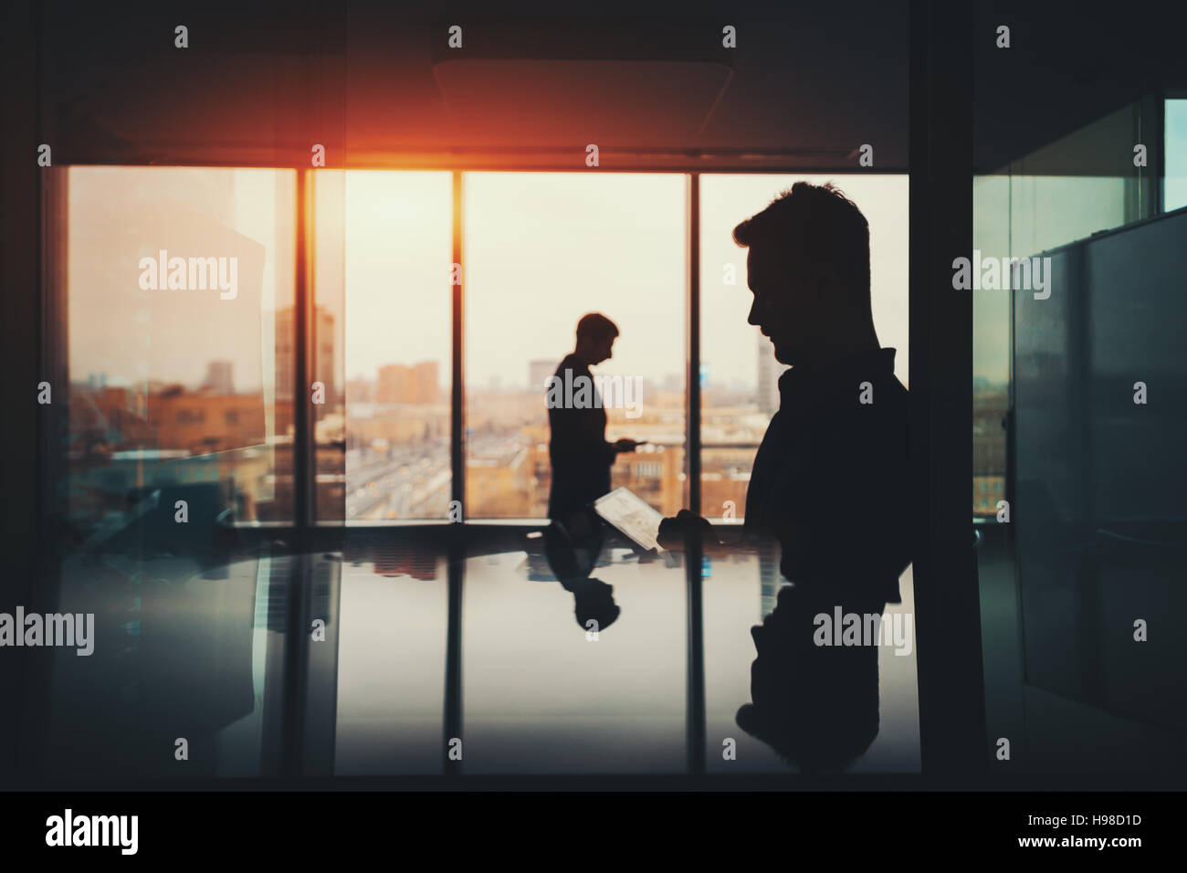 Silhouette of two businessmen working with their gadgets in office interior of skyscraper, man in front with digital Stock Photo