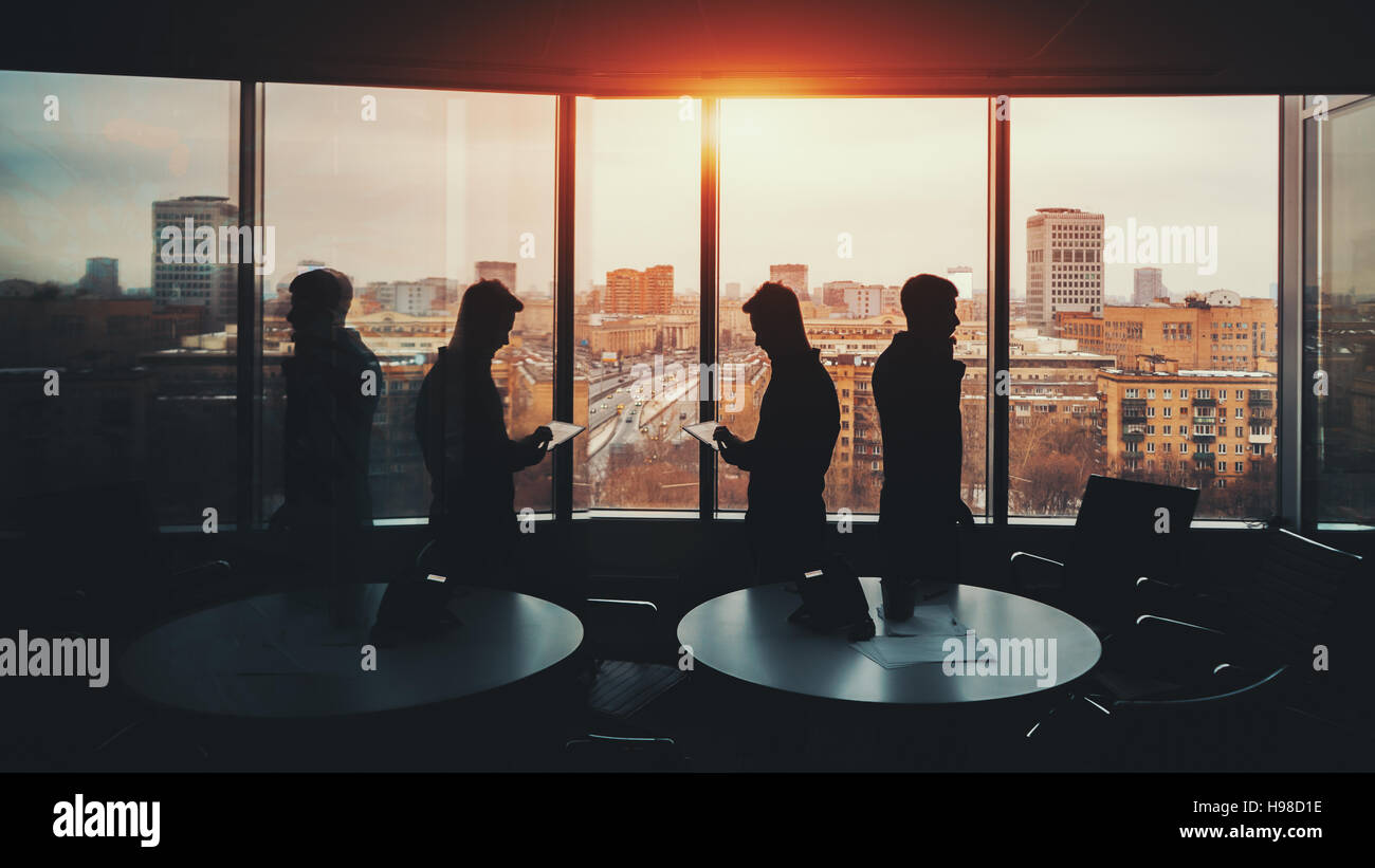 Silhouette of two businessmen with their gadgets in office interior of skyscraper, man on the left with digital - Stock Image