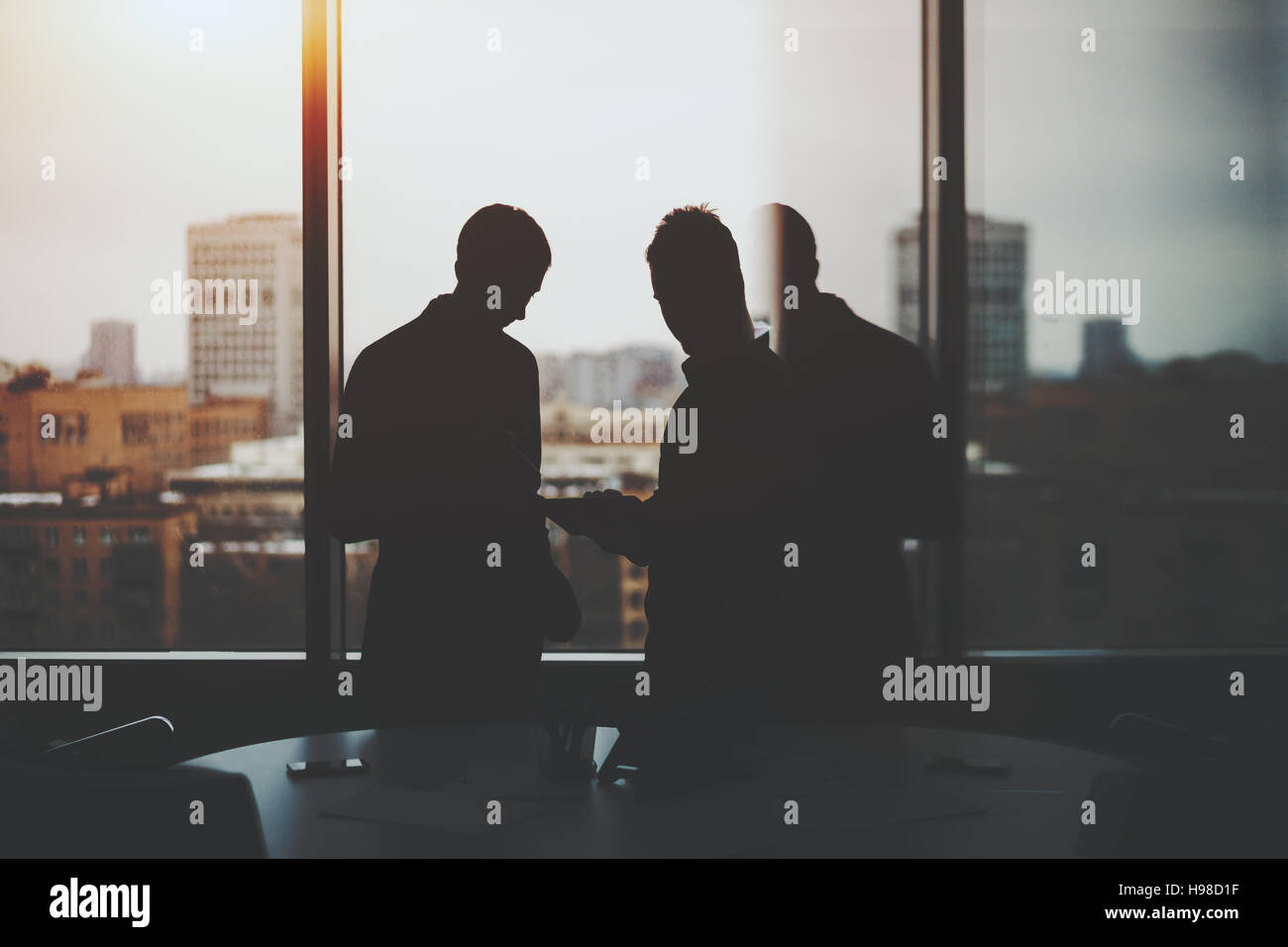 Silhouettes of two businessman near window and table of dark office interior, discussing something and looking on - Stock Image