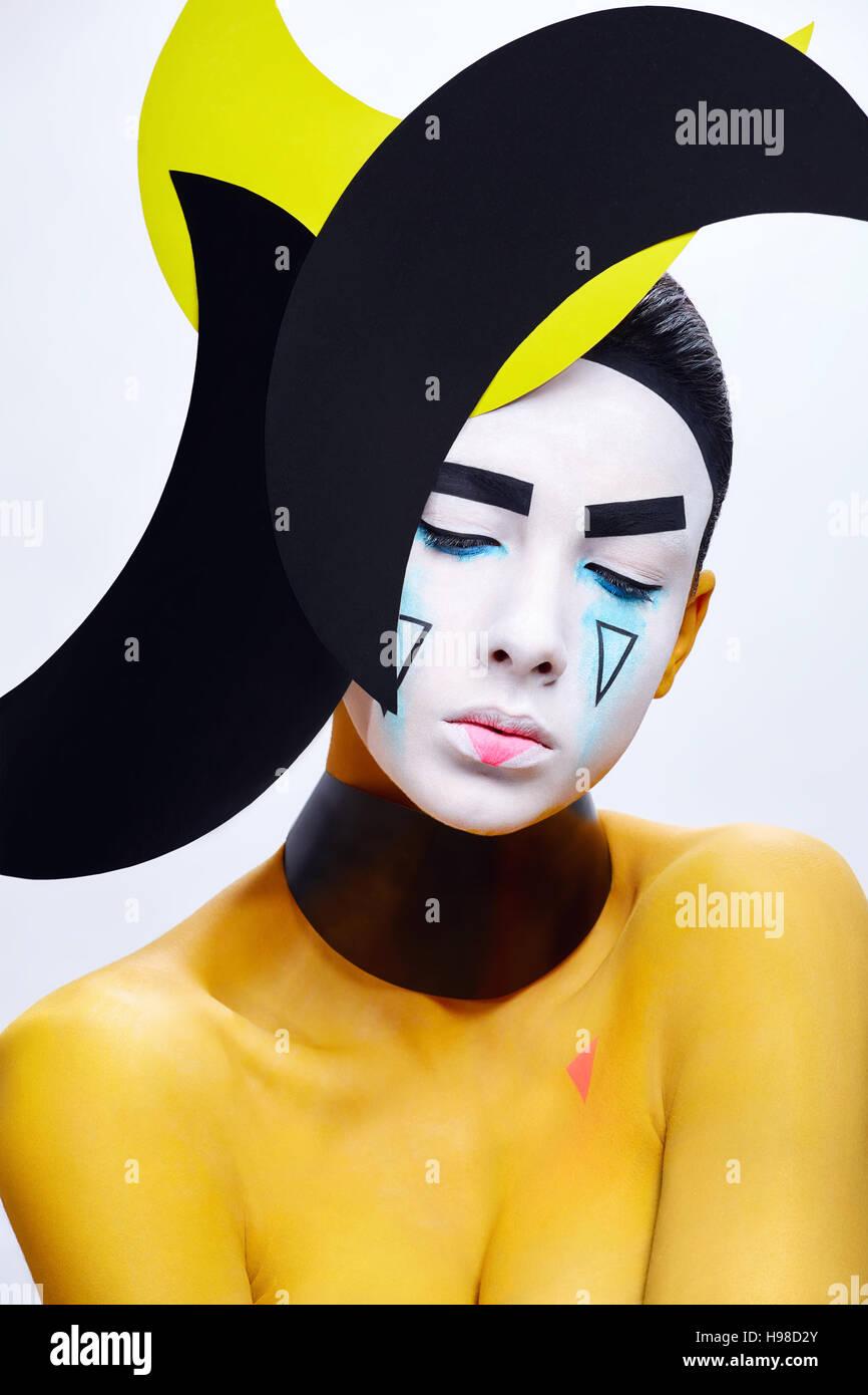Yellow paint bodyart. Young girl. Geometric headpiece. - Stock Image