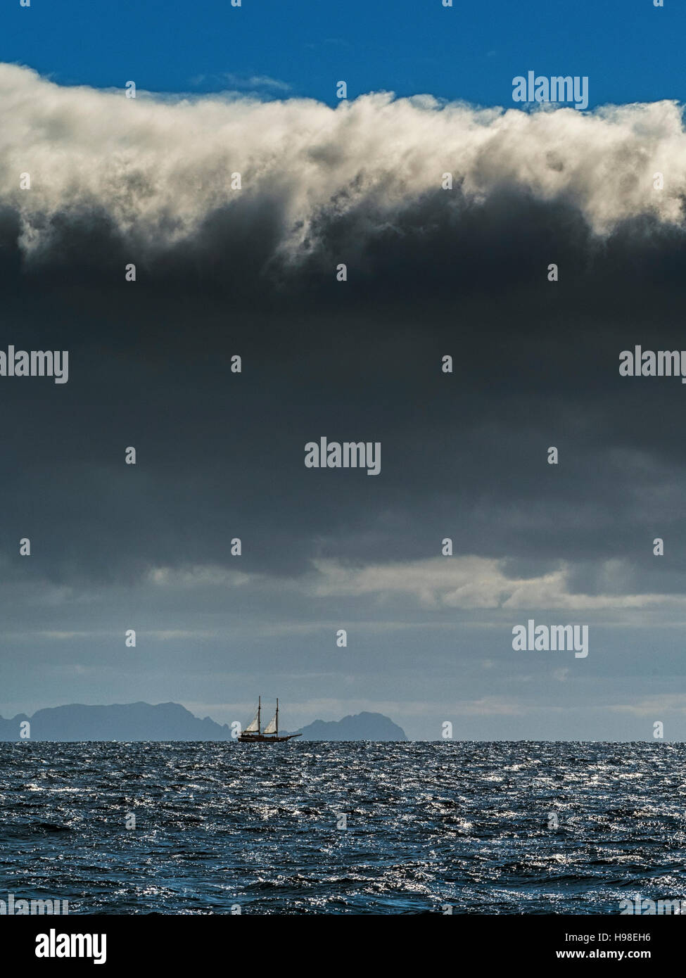 Deserted Islands: a two-masted boat sails past Ilhas Desertas, a small archipelago off the coast of Madeira, Portugal - Stock Image