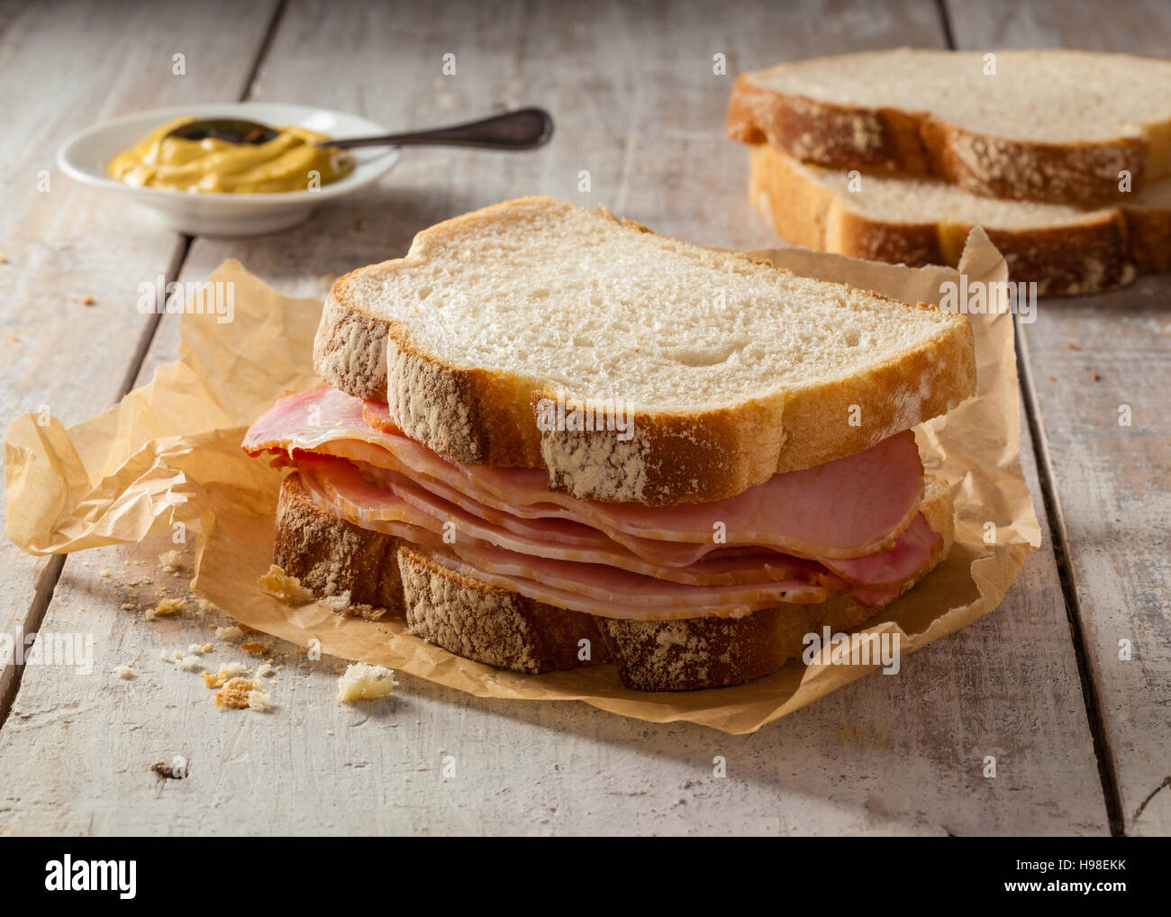 A smoked meat sandwich on a wooden table with mustard. - Stock Image