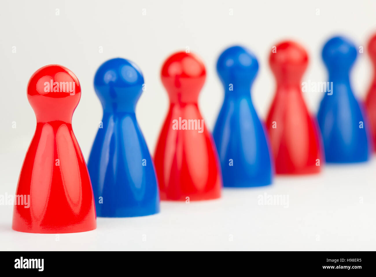 Conceptual game pawns that visualize the concept chain cooperation - Stock Image
