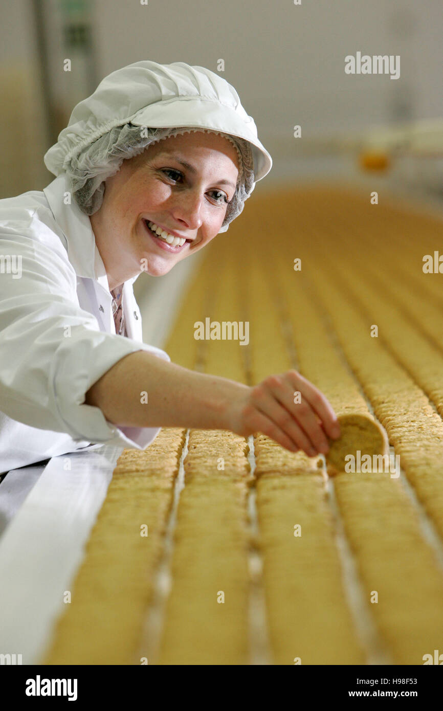 Production line with biscuits and factory workers - Stock Image