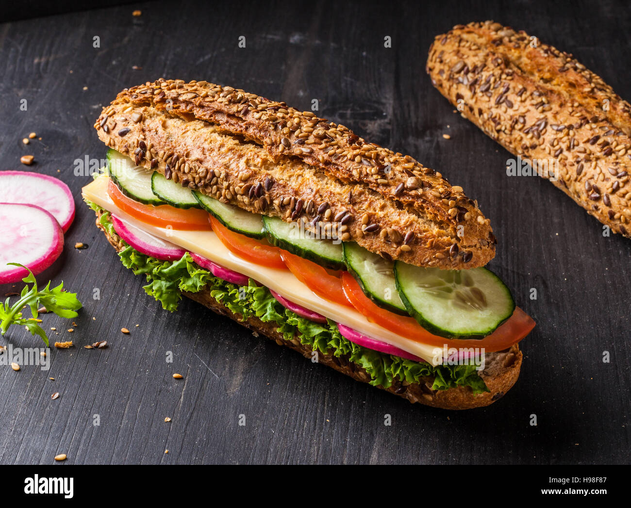Sandwich with cheese, tomato, cucumber, radish and lettuce. Dark and moody. - Stock Image