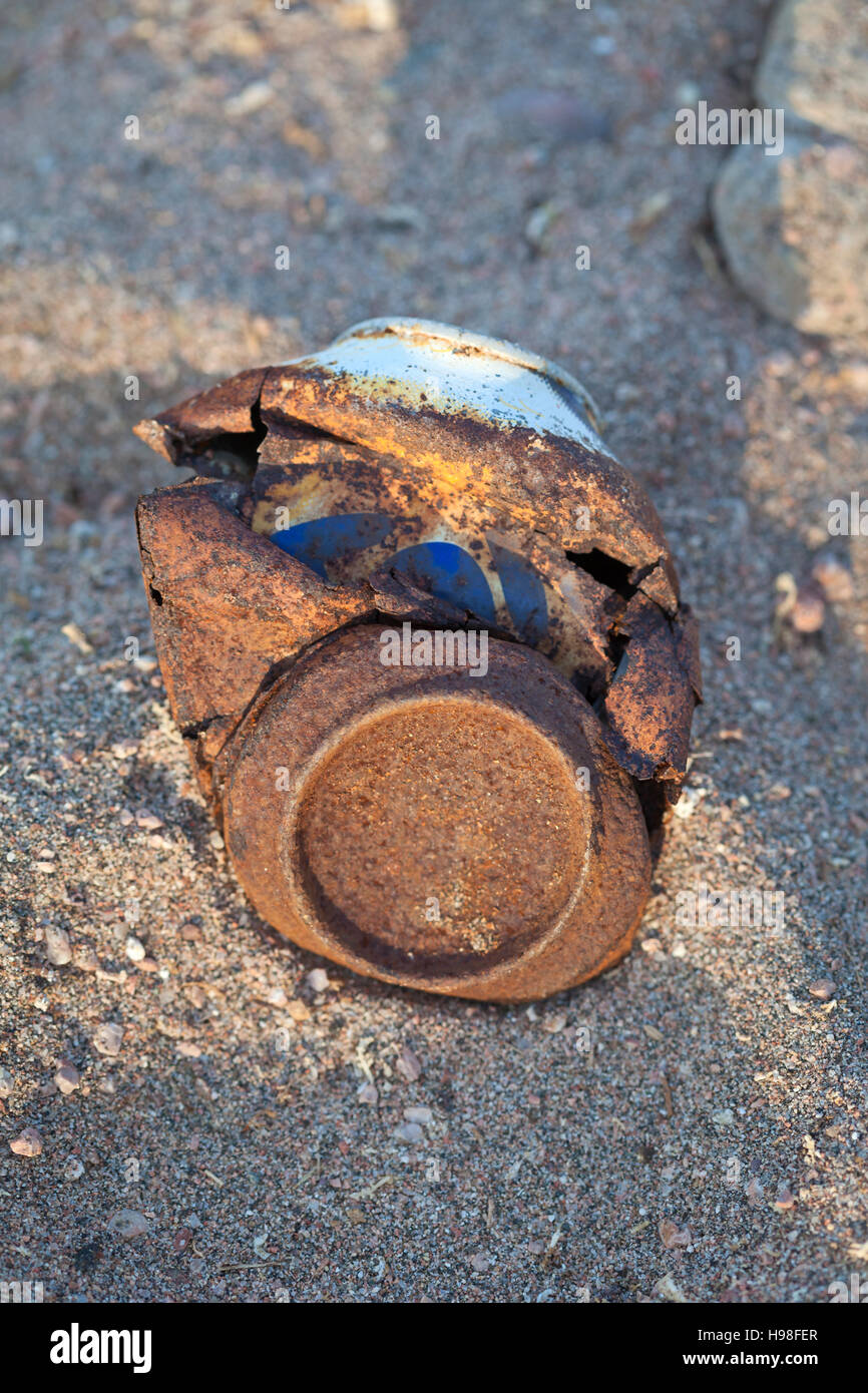 A rusty can littering a sandy beach, Egypt - Stock Image