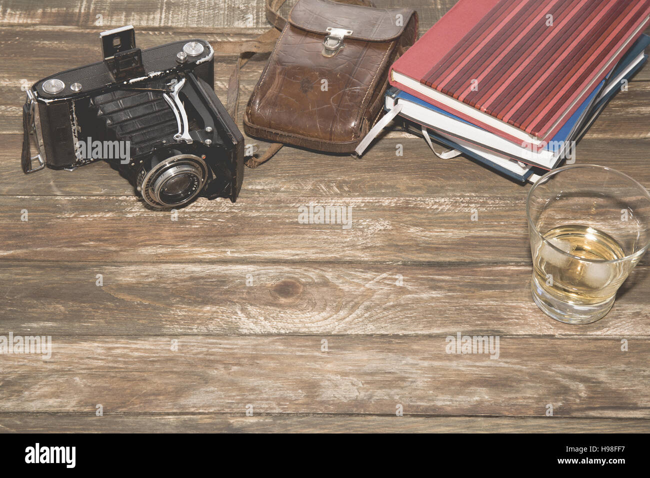 Old photocamera with leather case, notebooks on vintage wood background - Stock Image