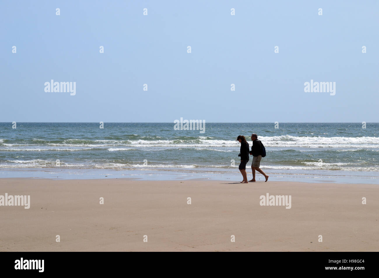A man and woman walking barefoot along a deserted beach in Wales with waves breaking in the background. Stock Photo