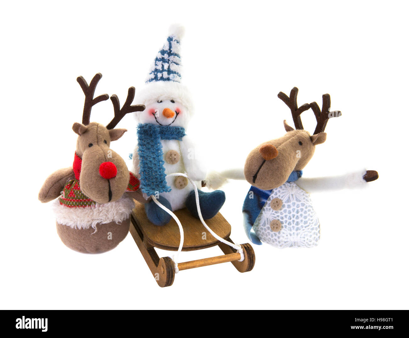 Snowman on a sledge with reindeer on a white background. - Stock Image