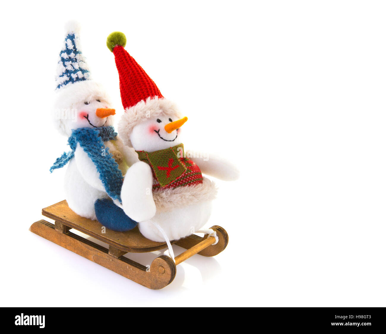 Two Snowmen on a sledge on a white background. - Stock Image