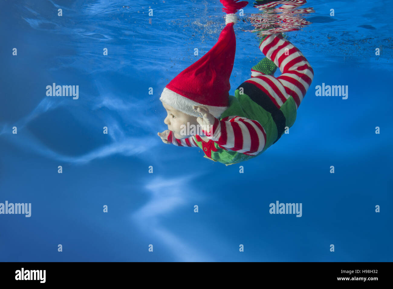 a little boy dressed as santas helper floats under water in the pool stock image