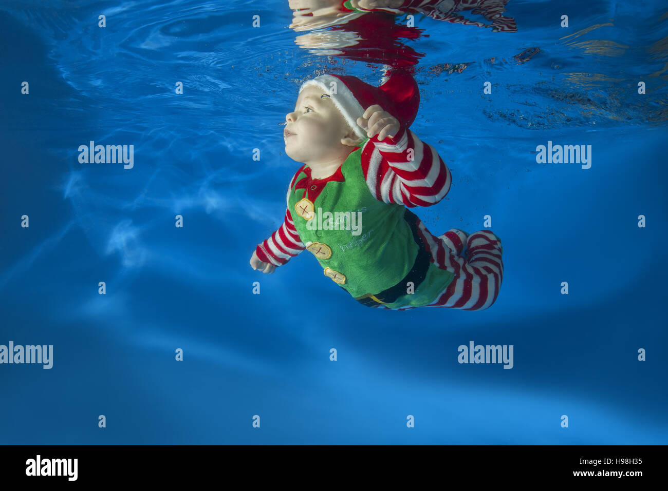 a little boy dressed as santas helper floats under water in the pool