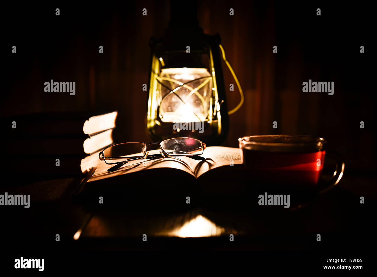 The light of a kerosene lamp and open book on the table - Stock Image