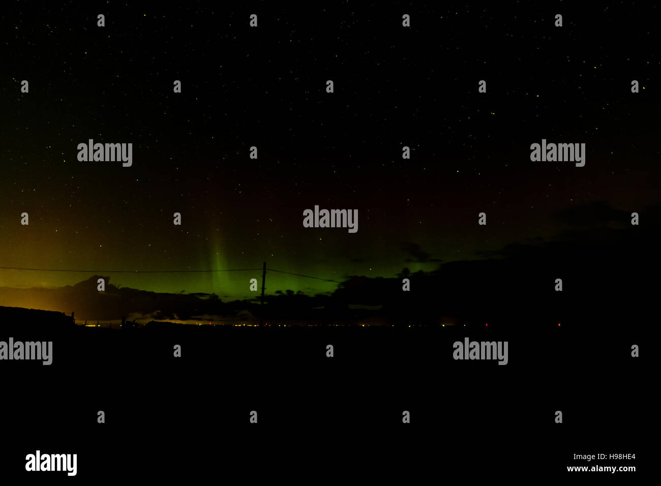northern lights seen over scottish northen sea and an oronind shooting star - Stock Image