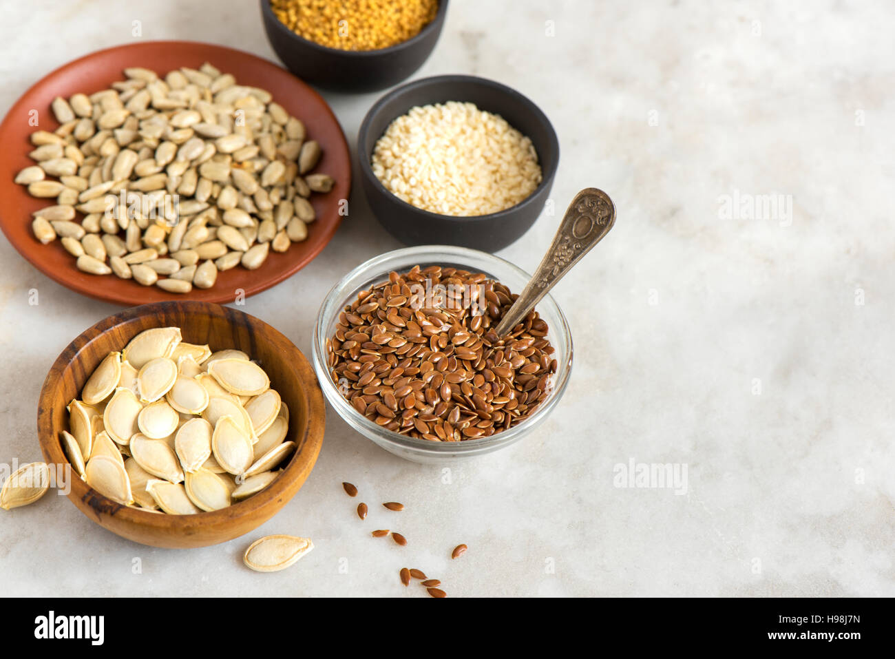 Assorted oil seeds (flax, sesame, pumpkin, sunflower, mustard) on stone background with copy space - organic ingredients - Stock Image