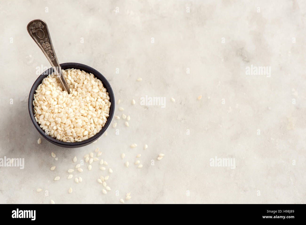 Sesame seeds in bowl over white stone background with copy space - healthy food ingredient - Stock Image