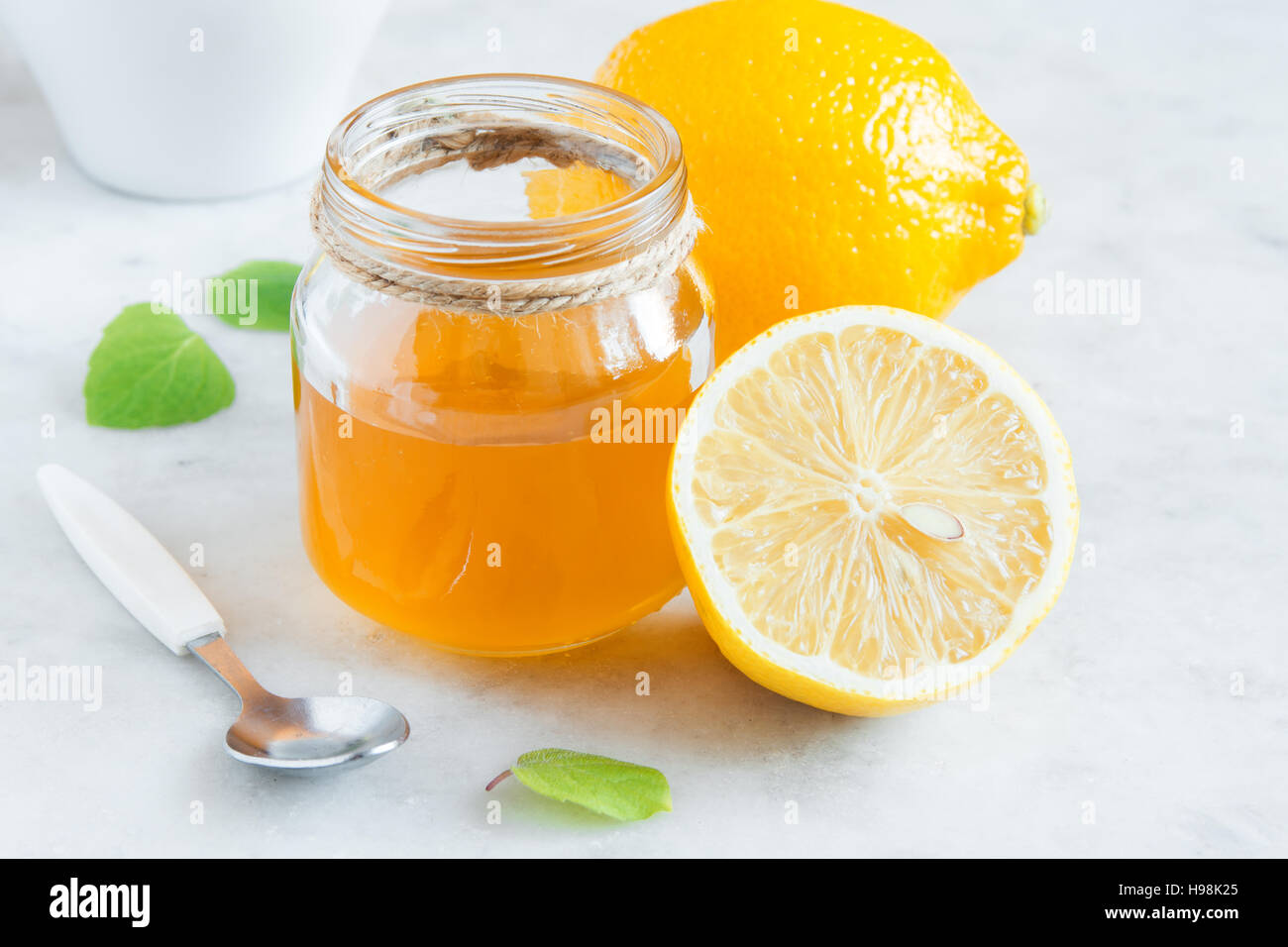 Lemon and honey over white stone background close up - healthy organic products for alternative medicine and healthy - Stock Image