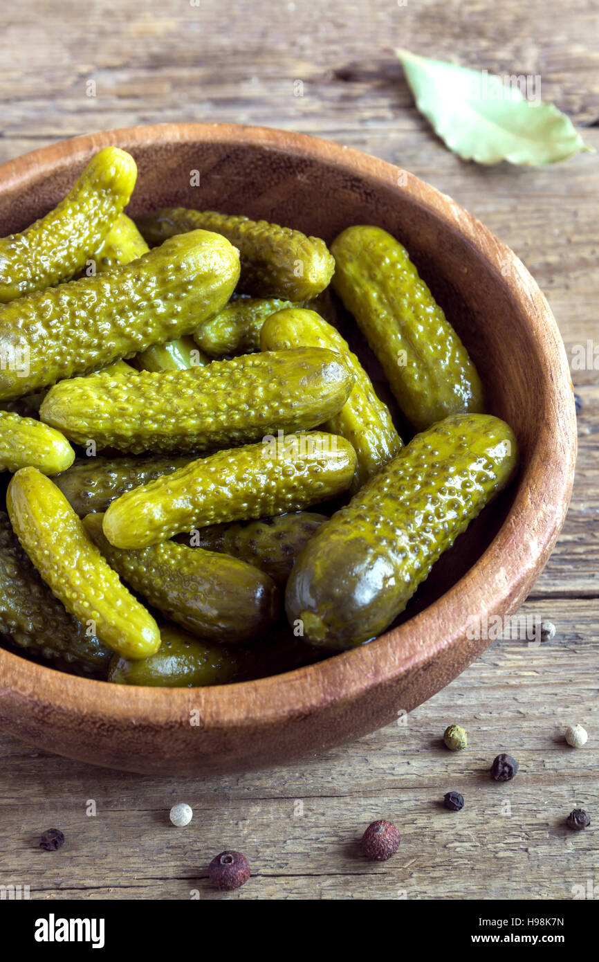 Pickles. Bowl of pickled gherkins (cucumbers) over rustic wooden background close up. - Stock Image