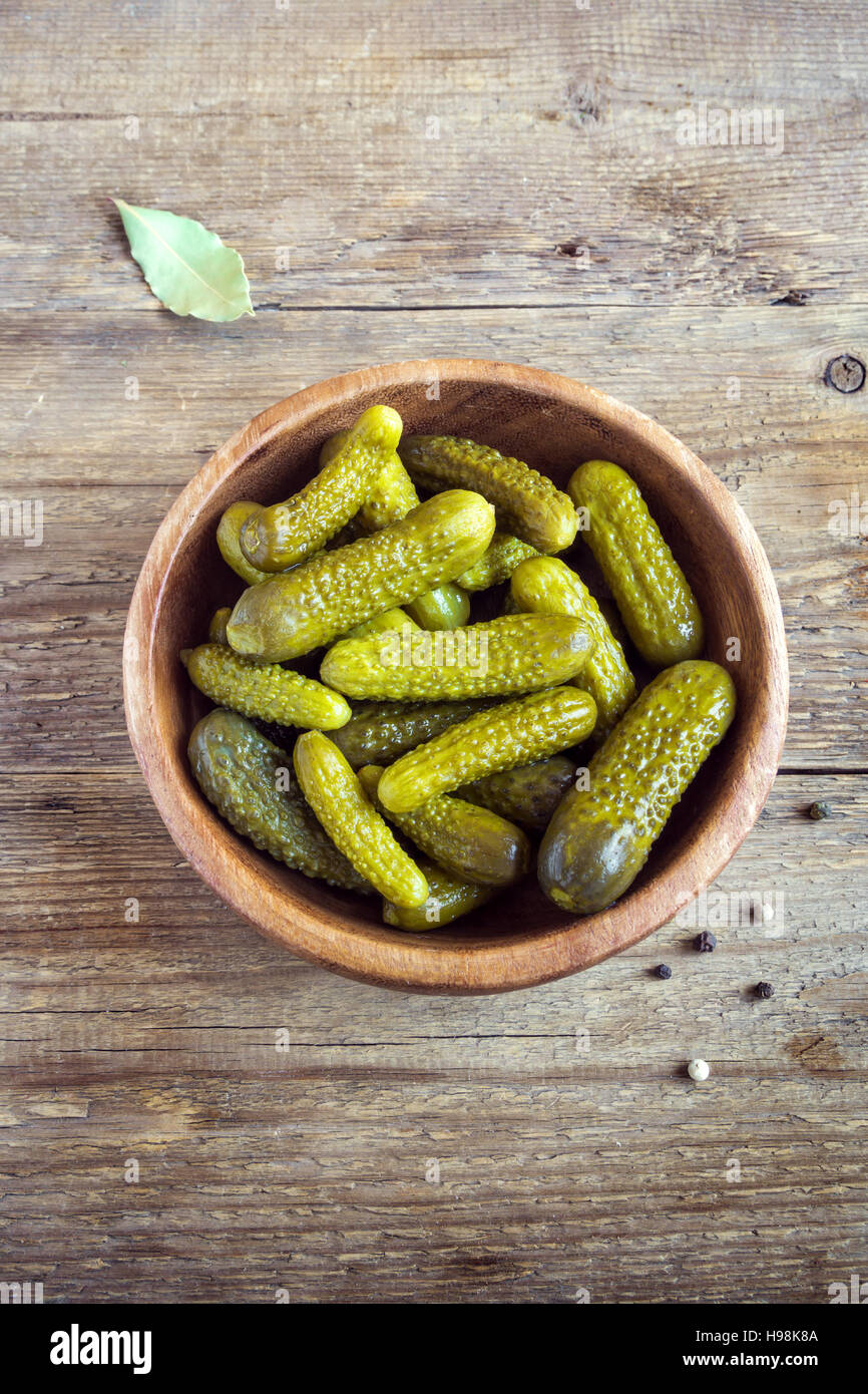 Pickles. Bowl of pickled gherkins (cucumbers) over rustic wooden background with copy space. - Stock Image