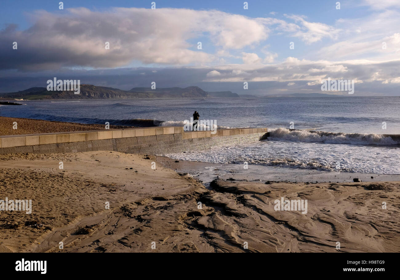 Lyme Regis Dorset, UK. 20th Nov, 2016. A walker enjoys the calm weather in Lyme Regis early this morning after the - Stock Image