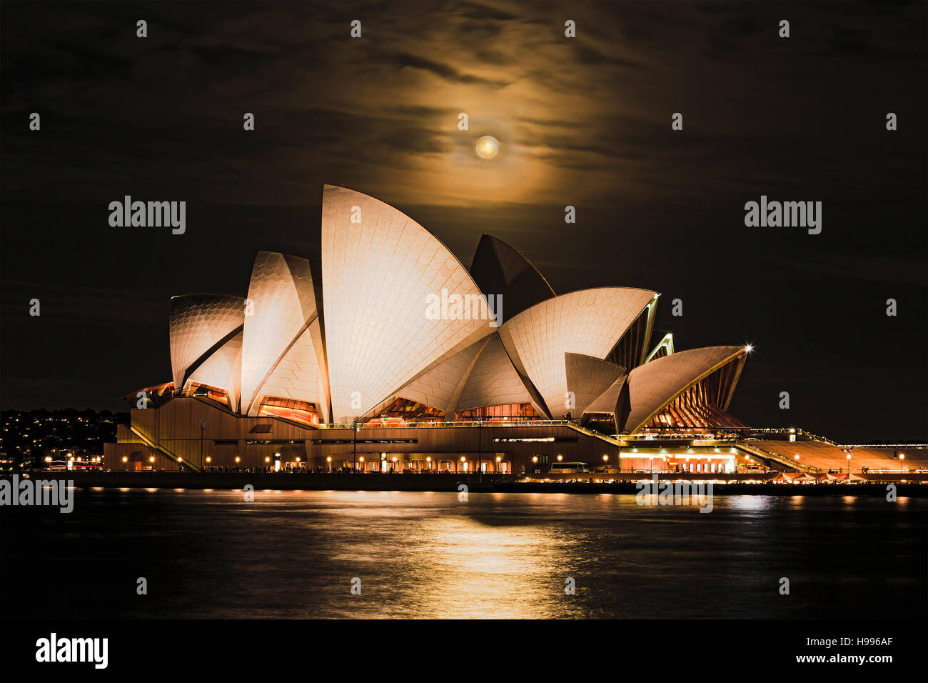 Sydney, Australia - 15 November 2016: Super full rusty moon rising over Sydney Opera House in Australia during unique - Stock Image