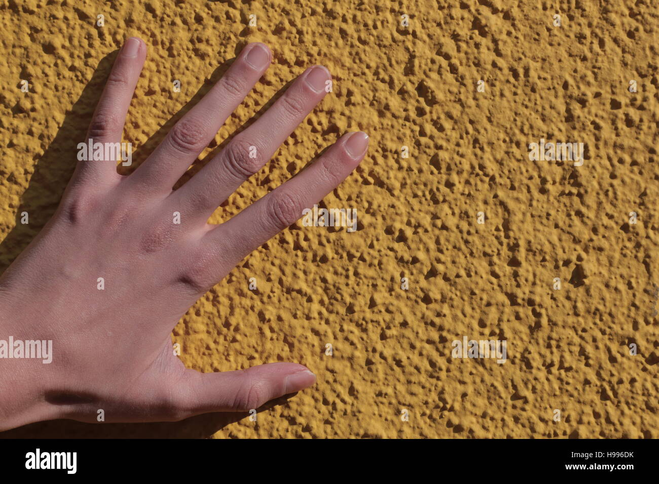 A hand on a yellow grainy wall - Stock Image