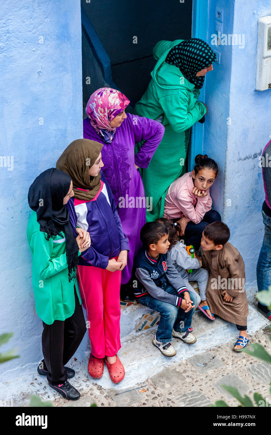 A Moroccan Family Watching The Life In Their Street From Their Front Door, Chefchaouen, Morocco - Stock Image