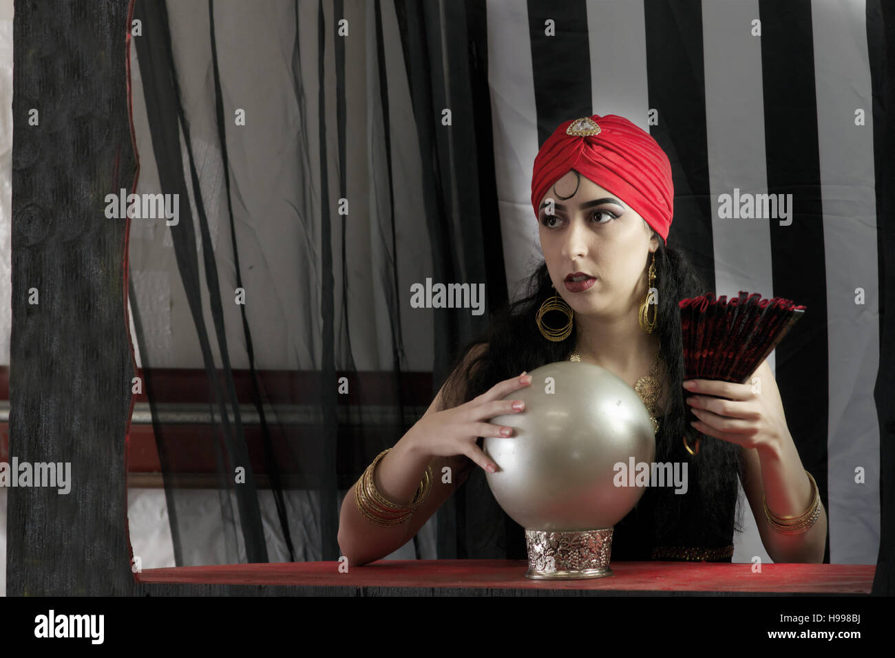 Beautiful young female with  crystal ball ready to read the future in circus setting - Stock Image