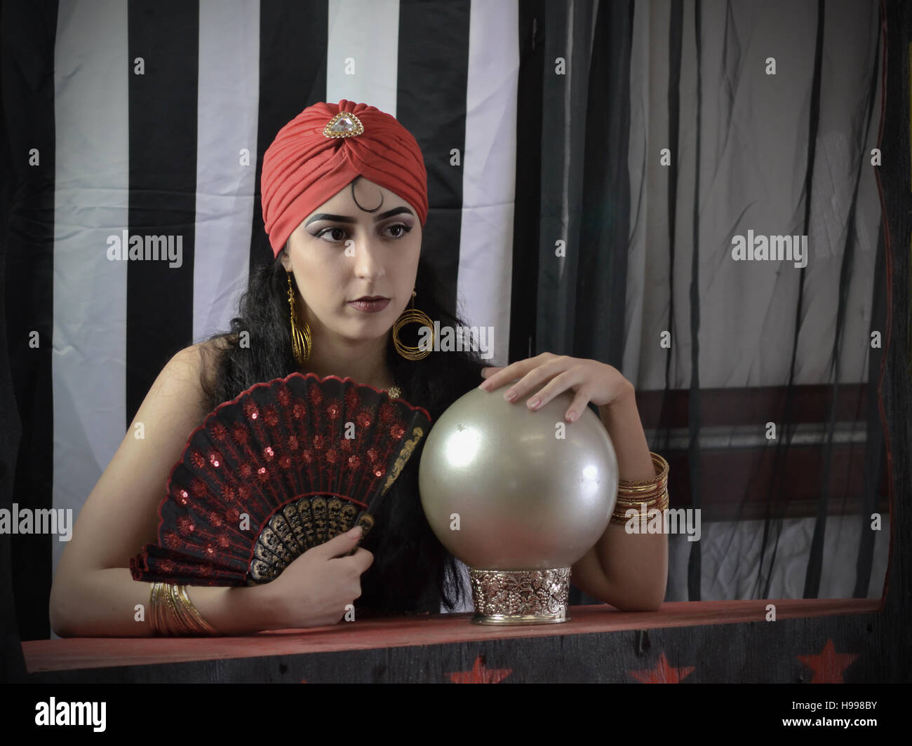 Performer with  crystal ball and fan ready to read the future in circus setting - Stock Image