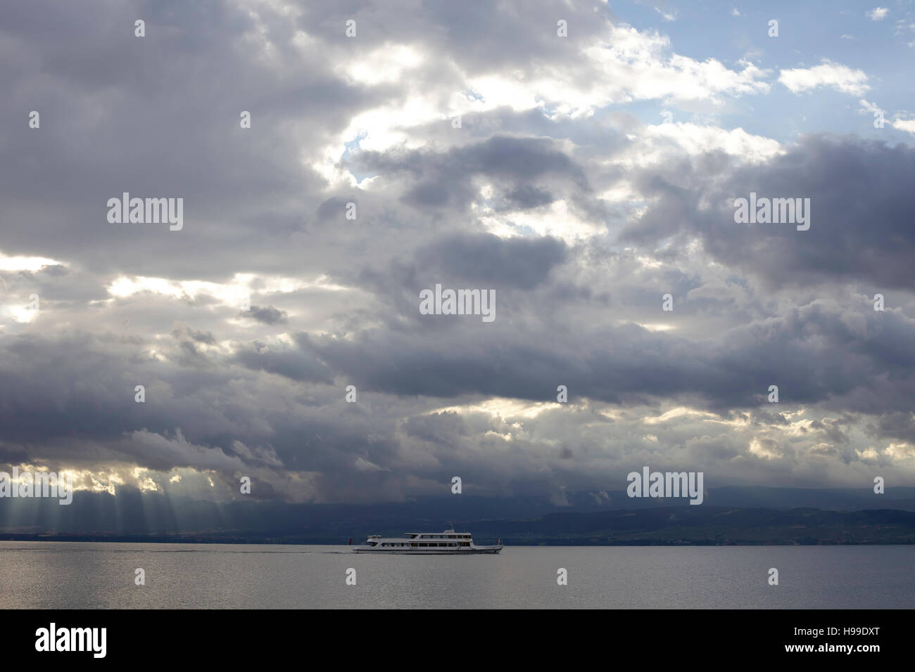 Ferry boat sailing on Lake Geneva under heavy cloud. Stock Photo