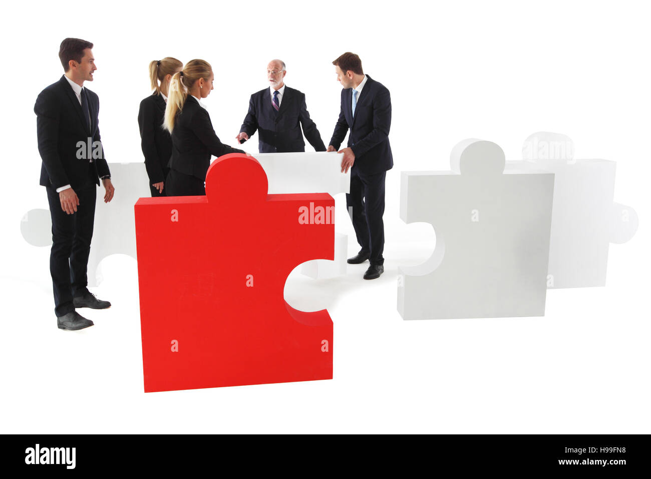 Group of business people assembling pieces of a puzzle isolated on white background - Stock Image