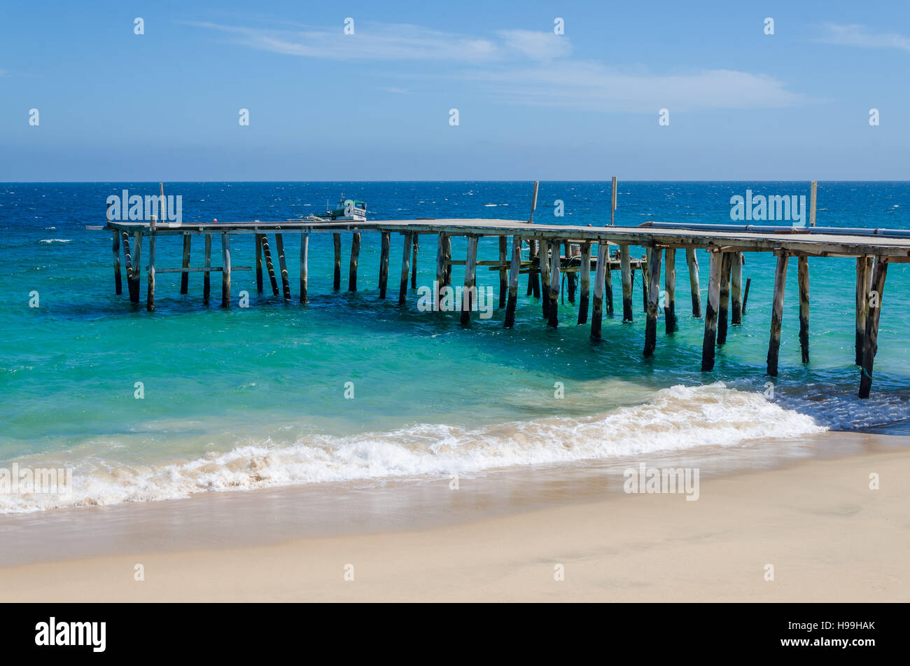 Long simple wooden jetty leading into turquoise blue ocean at small fishing village Mucuio in Angola. - Stock Image